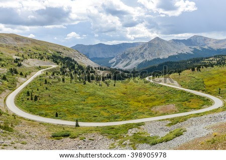 Summer Mountain Road - Late summer view of scenic mountain road near the summit (12,126 ft/3,696 m) of the Cottonwood Pass - a high mountain pass between Buena Vista and Crested Butte, Colorado, USA.  - stock photo