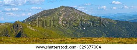 Summer mountain view with snow on mountainside (with observatory ruins on Chornogora Ridge, Ukraine). - stock photo