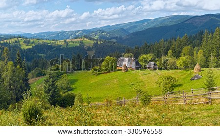Summer mountainous green glade with small country estate (Slavske village, Carpathian, Ukraine).