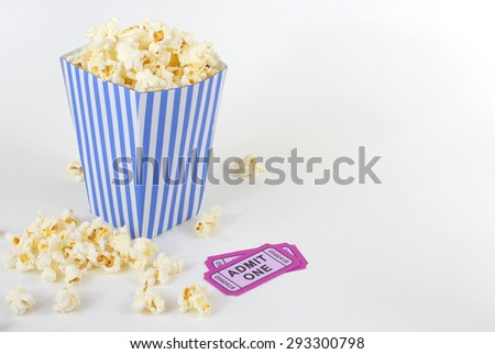 Summer movie theme with a blue and white striped bucket full of popcorn and two purple movie tickets. Popcorn is scattered about white background. - stock photo