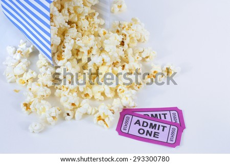 Summer movie theme with popcorn falling out of a tipped over blue and white striped bucket with two purple movie admission tickets. Popcorn is scattered about white background. Copy space. - stock photo