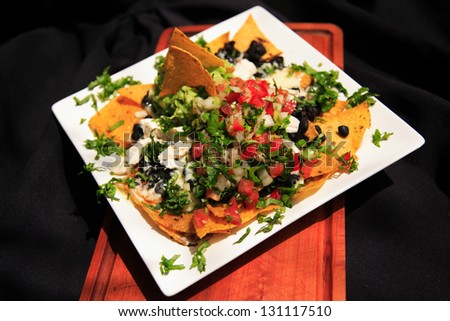 Summer Nachos with cheese and chicken served on a white plate - stock photo