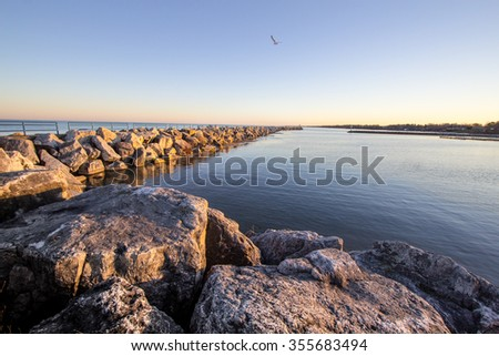 Summer On The Great Lakes Shore. Coastal Great Lakes harbor bathed in the golden glow of the warm summer sun. Tierney Park. Lexington, Michigan. - stock photo