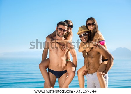 Summer on the sea. Youth rest. Honeymoon. Rest near the ocean. Friendly company on the beach. Young sunbathes on the beach. - stock photo