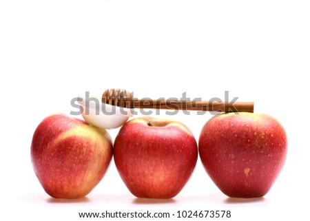 Summer or autumn crops concept. Apples placed in row isolated on white background. Wooden honey spoon on apples, close up. Line made of red apple fruits with saucer of honey on top