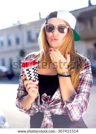 Summer outdoor fashion portrait of young stylish hipster cute girl drinking tasty coffee on the street and sending kisses ,casual trendy outfit, swag cap,checkered shirt and stylish sunglasses.