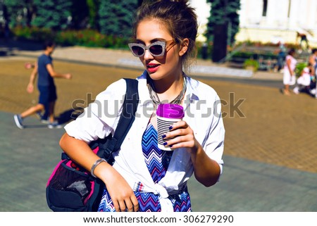Summer outdoor fashion portrait of young stylish hipster girl drinking tasty coffee on the street , traveling with back pack, extravagant sunglasses, bright trendy outfit, toned Instagram colors. - stock photo