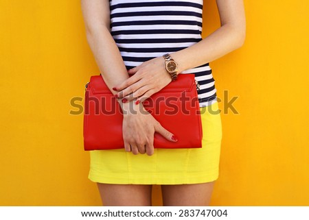 Summer outdoor fashion young woman with red bag clutch in hand closeup. Trendy outfit concept  - stock photo