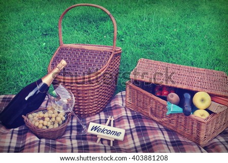 Summer Outdoor Picnic Scene On The Lawn With Sign Welcome, Wicker Basket, Hamper, Blanket, Grape, Wine, Champagne, Fruits - stock photo