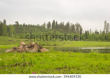 Summer outdoor recreation, Scandinavian vacation. Slide granite stones on shore of small lake surrounded by pine forest. Purhon Campsite, Hamina, Finland, Suomi - stock photo