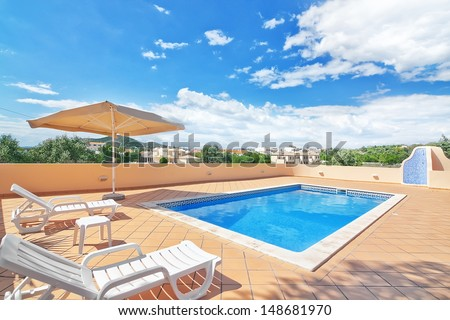 Summer outdoor swimming pool and sun loungers. In the hotel to rest. - stock photo