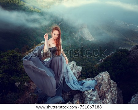 Summer outdoors portrait of beautiful furious scandinavian warrior ginger woman in grey dress with metal chain mail. High in the mountains, fog and mystery