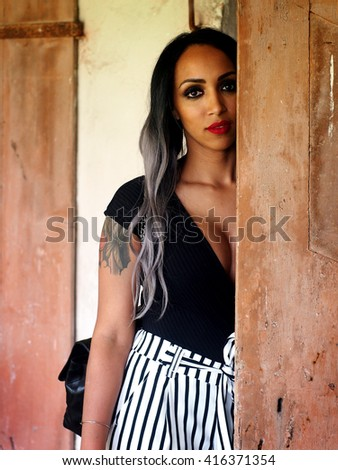 Summer Outfit - Beautiful african italian woman with granny hairstyle, black body, black and white striped pants, black high heels shoes, black leather bag, near an abandoned and ruined house. - stock photo