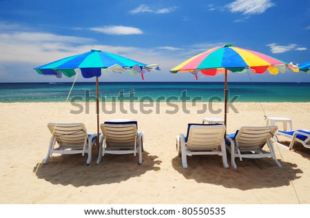 Summer paradise with whhite chair and colorful umbrella at Phuket beach, Thailand