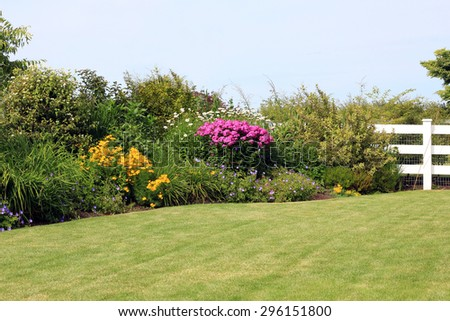Summer park garden lawn with perennial border in bloom.  - stock photo