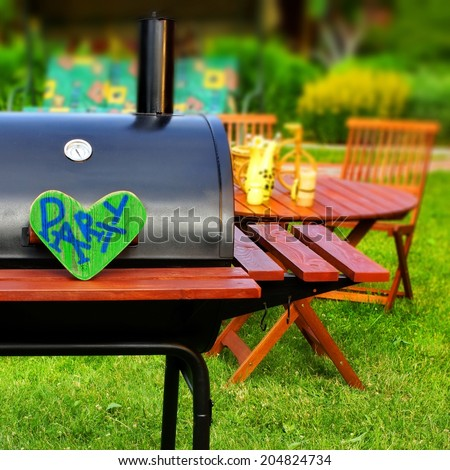"Summer Party Scene. BBQ Grill on the Lawn with sign ""Party"" on wooden heart. - stock photo"