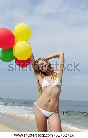 summer party : woman holding colorful balloons on the beach