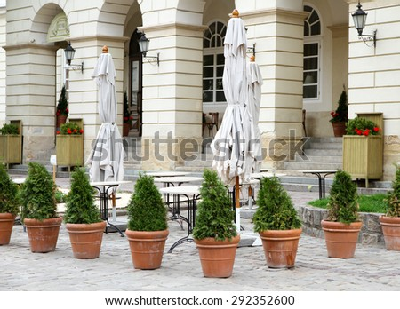 Summer patio of cafe with small trees in pots - stock photo