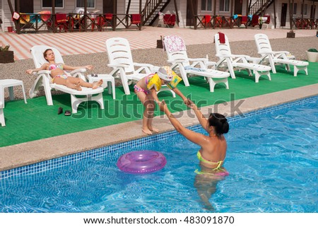 Summer 2016, pension near the Sea of Japan, Russia. Mom teaches a little girl jumping into the water (swimming pool).