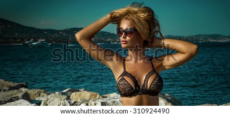 Summer photo of beautiful sexy blonde woman in elegant lace lingerie. Sunny day. Luxury resort. Girl wearing fashionable sunglasses. - stock photo
