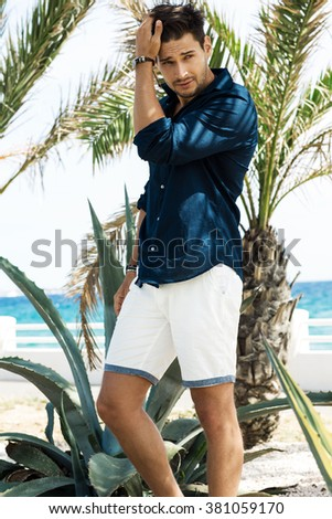 Summer photo of sexy model under the palm tree - stock photo