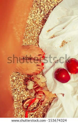 Summer picnic concept. Feet of standing woman in trendy dress near two red apples (love symbol). Wedding accessories on white vapory cloth. Sunny weather. Outdoor shot