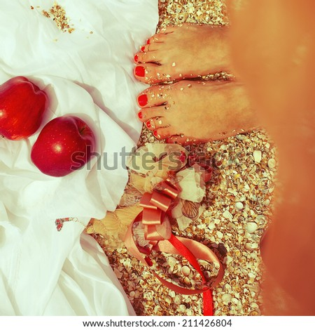 Summer picnic concept. Feet of standing woman in trendy dress near two red apples (love symbol). Wedding accessories on white vapory cloth. Sunny weather. Outdoor shot - stock photo