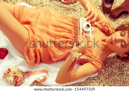 Summer picnic concept. Portrait of a happy young woman lying at the seaside in trendy dress, holding vintage photo-camera and shooting something. Sunny weather. Outdoor shot