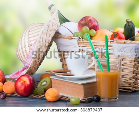 Summer picnic on wooden table with a basket of food, nature green background
