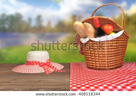 Summer Picnic Scene At Countryside Lake. White Straw Hat And Picnic Wicker Basket Close Up With Red Wine Bottle, French  Baguettes, Fruits  On The Wood Table. - stock photo