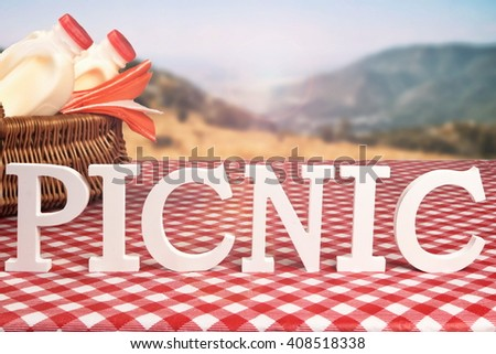 Summer Picnic Scene In The Mountain.  White Wooden  Sign Picnic, Wicker Basket Close Up With Bottles Of Milk  On The Red Checkered Tablecloth - stock photo