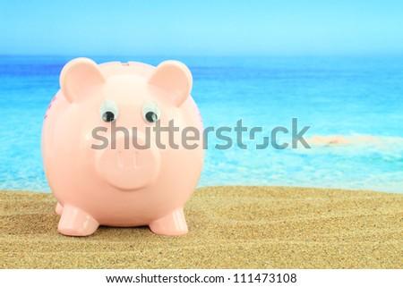 Summer piggy bank on the beach - stock photo