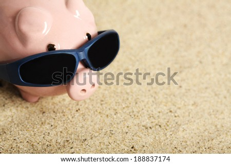 Summer piggy bank with sunglasses standing on the beach  - stock photo