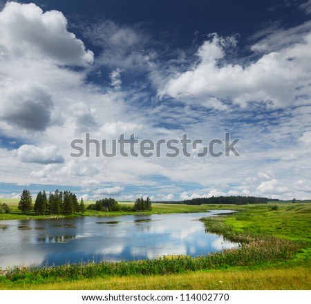 Summer pond with green meadows around and blue cloudy sky - stock photo