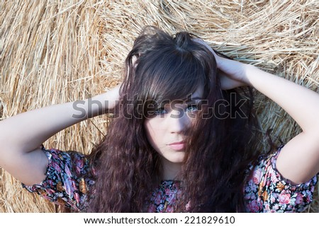 summer portrait of a beautiful country girl on a background of straw.