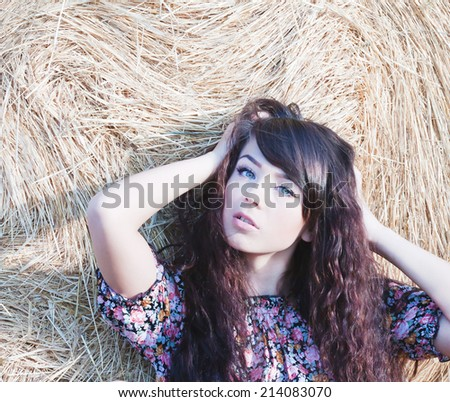 summer portrait of a beautiful longhair country girl on a background of straw.Photo tinted light yellow to transfer summer atmosphere