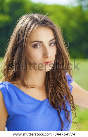 Summer portrait of a beautiful young brunette Caucasian girl in blue dress outdoors in the park