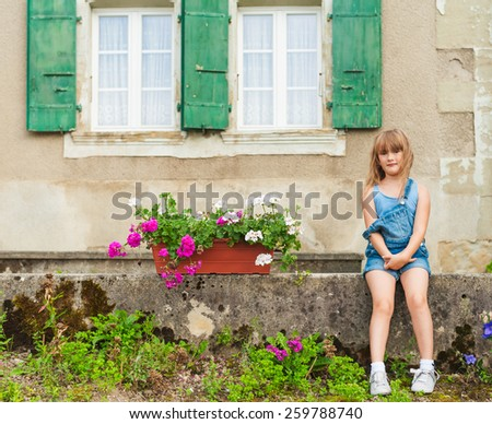 Summer portrait of a cute little girl of seven years old sitting in the yard - stock photo