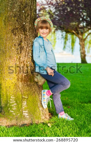 Summer portrait of a cute little girl of 6 years old, wearing blue clothes, colorful hat and shoes, standing next to the tree in the park - stock photo