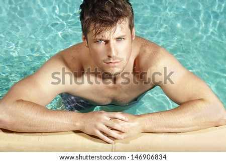 Summer portrait of a handsome young cool guy in the pool