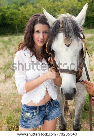 Summer portrait of a young woman with her favorite farm horse - stock photo