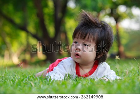 Summer portrait of beautiful baby girl on the lawn - stock photo