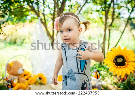 Summer portrait of beautiful baby girl with sunflowers in park.photo zone is decorated with sunflowers and bees.