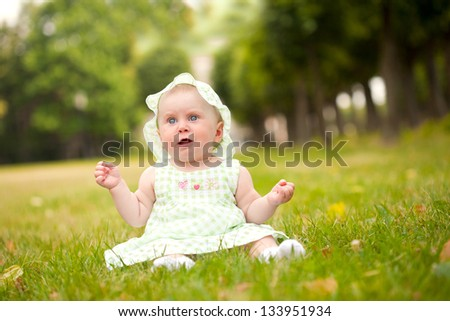 Summer portrait of beautiful baby on the lawn