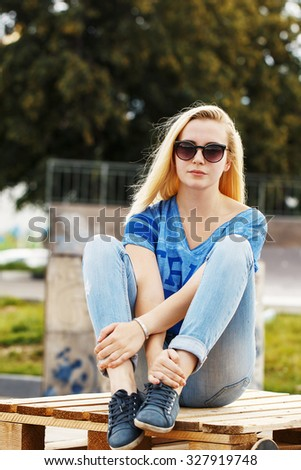 summer portrait of cute calm serious young girl with blond hair sunglasses and blue jeans seating in park. Outdoor photo