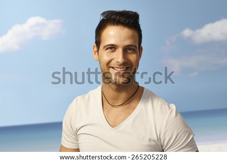 Summer portrait of handsome young man smiling happy on the beach. - stock photo