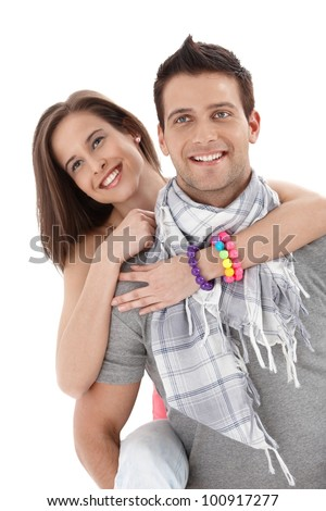 Summer portrait of happy couple, handsome man carrying pretty girlfriend on back, laughing.