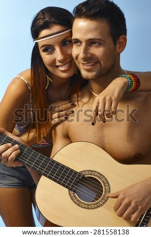 Summer portrait of happy loving couple embracing, man holding guitar. - stock photo