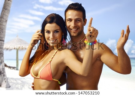 Summer portrait of happy loving couple on the beach, embracing, having fun.