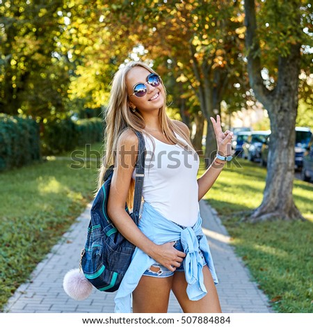 Summer portrait of happy smiling young blonde woman having fun outdoor